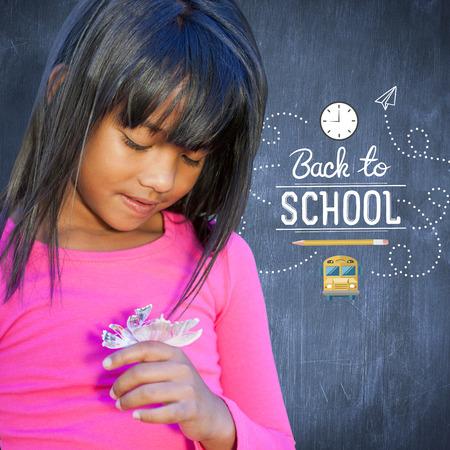 girl holding flower: Cute little girl holding flower against blue chalkboard