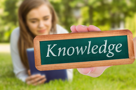 university word: The word knowledge and hand showing chalkboard against university student lying and using tablet pc Stock Photo