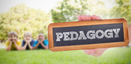 pedagogy: The word pedagogy and hand showing chalkboard against happy friends in the park Stock Photo