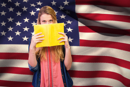 covering the face: Student covering face with book in library  against digitally generated american national flag