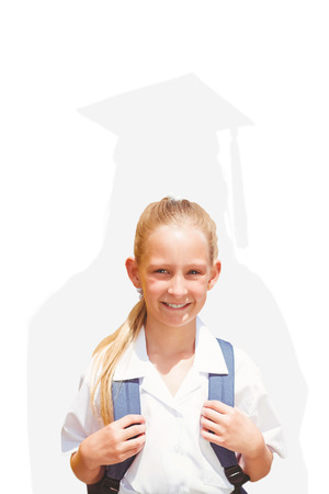 academic robe: Cute pupil smiling at camera by the school bus against silhouette of graduate
