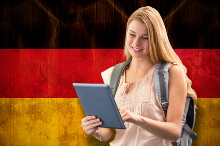 scrolling: Happy student using tablet against germany flag in grunge effect