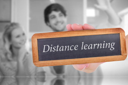envisioning: The word distance learning and hand showing chalkboard against colleagues envisioning an idea together