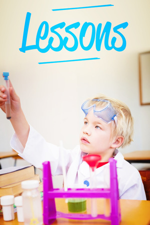 make believe: The word lessons against cute pupil dressed up as scientist in classroom Stock Photo