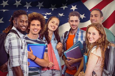 personas mirando: Grupo sonriente de estudiantes con carpetas contra generada digitalmente bandera nacional americana