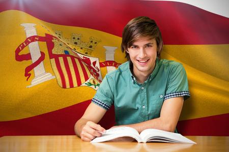 bookshelf digital: Student sitting in library reading  against digitally generated spanish national flag