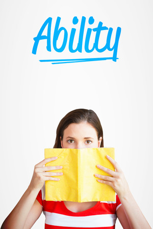 covering face: The word ability and student covering face with book in library against white background with vignette