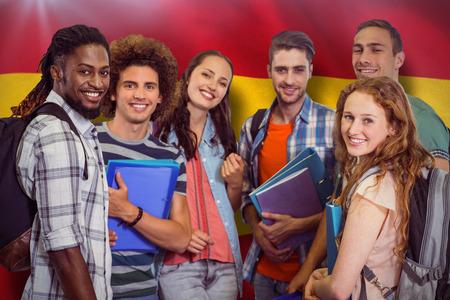 man holding: Smiling group of students holding folders against digitally generated spanish national flag Stock Photo