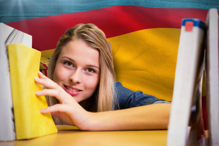 girl studying: Pretty student in the library against digitally generated spain national flag