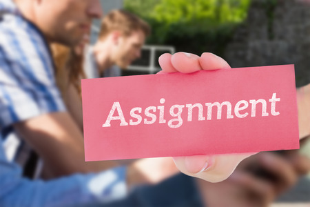 assignment: The word assignment and hand showing card against happy students sitting in a row texting