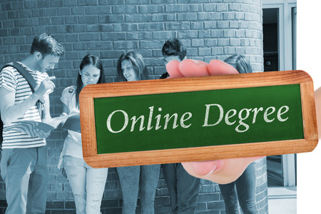 online degree: The word online degree and hand showing chalkboard against happy students standing and reading