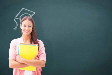 Pretty student smiling at camera against teal, blue Stock Photo