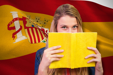 covering the face: Student covering face with book in library  against digitally generated spanish national flag