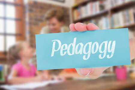 pedagogy: The word pedagogy and hand showing card against teacher helping pupils in library