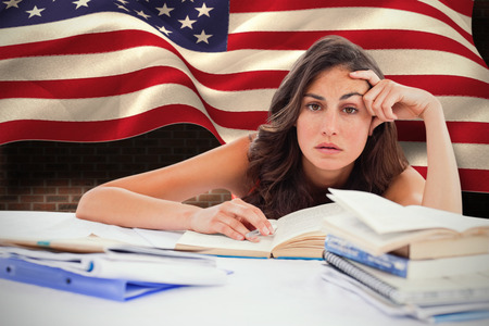 bored student: Bored student doing her homework against composite image of digitally generated united states national flag Stock Photo