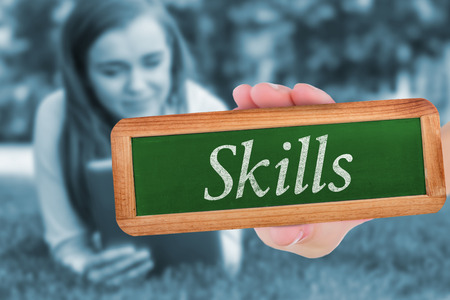 university word: The word skills and hand showing chalkboard against university student lying and using tablet pc