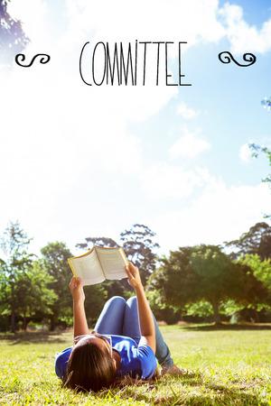comité d entreprise: Le comité de mot contre jolie femme lisant dans le parc Banque d'images