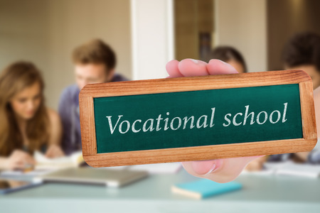 revising: The word vocational school and hand showing chalkboard against smiling friends students revising together