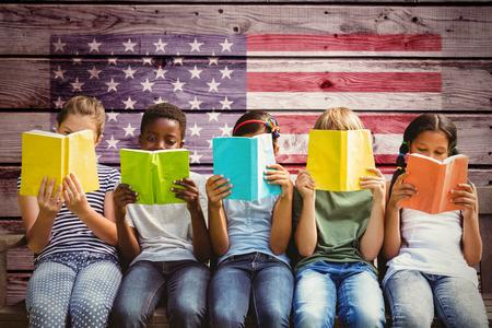 niños negros: Niños que leen los libros en el parque contra imagen compuesta de la bandera nacional de EE.UU.