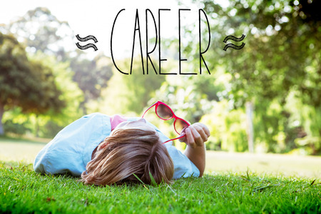 The word career against pretty woman lying down in park