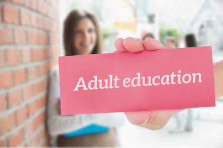 adult student: The word adult education and hand showing card against pretty student smiling and holding notepads Stock Photo