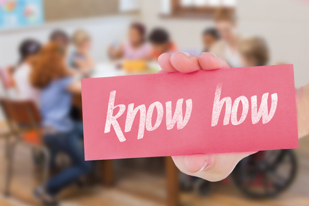 knowhow: The word know-how and hand showing card against pretty teacher helping pupils in classroom