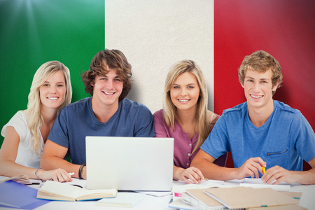 a study: A group of students with a laptop look into the camera against italy national flag Stock Photo