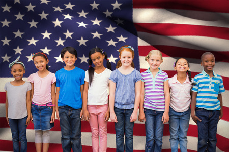 Cute pupils smiling at camera in classroom against digitally generated american national flag