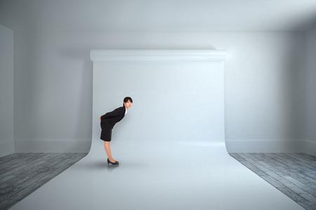 bending: Serious businesswoman bending against large white screen