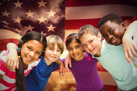 amabilidad: Niños felices que forman corrillo en el parque contra imagen compuesta de estados unidos generados digitalmente la bandera nacional Foto de archivo