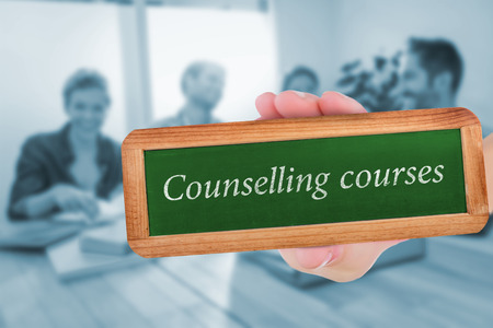 counselling: The word counselling courses and hand showing chalkboard against group of colleagues reading books