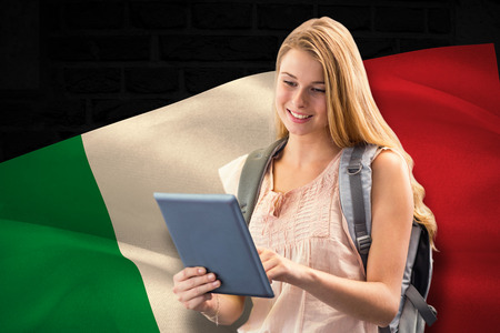 scrolling: Happy student using tablet against digitally generated italy national flag