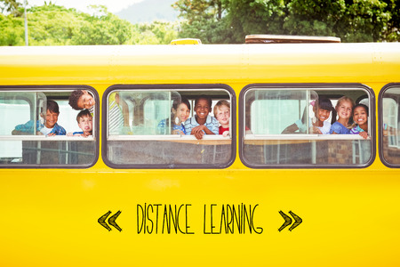 The word distance learning against cute pupils smiling at camera in the school bus