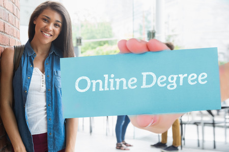 online degree: The word online degree and hand showing card against pretty student smiling at camera with classmates behind