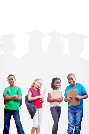 graduacion ni�os: alumnos lindos sonriendo a la c�mara contra la silueta del graduado