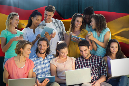rippling: Several students using electronic devices against digitally generated spain flag rippling Stock Photo