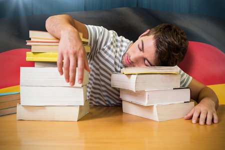 slump: Student asleep in the library against digitally generated german national flag