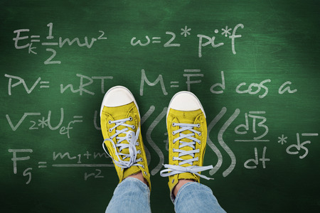 theories: Casual shoes against green chalkboard Stock Photo