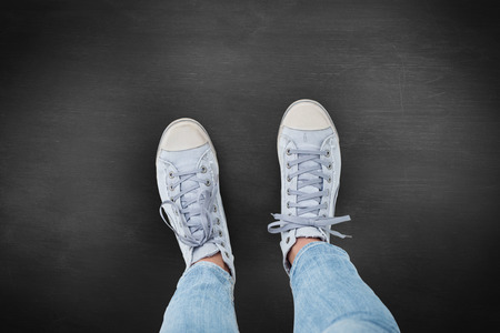 shoestring: Woman wearing trainers  against black background