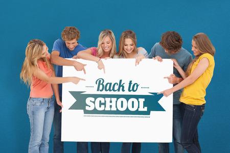 hoja en blanco: Un grupo que sostiene una hoja en blanco y apuntando a él contra el fondo azul Foto de archivo