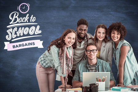 adult student: Fashion students working as a team  against blue chalkboard Stock Photo
