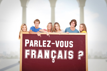francais: Smiling group of people with a blank space as they point to it against bright room with columns Stock Photo