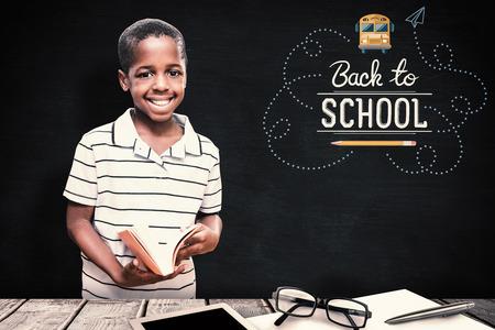 niños negros: estudiante feliz con el libro contra la pizarra