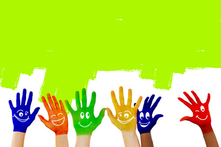green smiley face: Hands with colourful smiley faces against green vignette