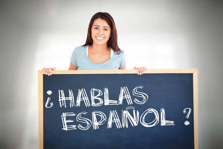 spanish woman: Attractive woman holding a  board against room overlooking city Stock Photo