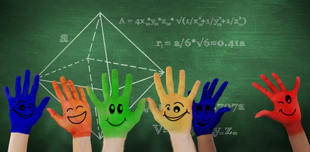 green smiley face: Hands with colourful smiley faces against green chalkboard