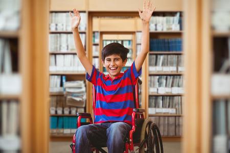 niños discapacitados: El muchacho en silla de ruedas en el pasillo de la escuela frente a la biblioteca Foto de archivo