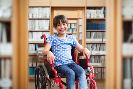 niños discapacitados: Linda alumno discapacitado sonriendo a la cámara en el pasillo frente a la biblioteca