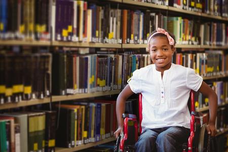 persona en silla de ruedas: Niña sentada en la silla de ruedas en el pasillo de la escuela en contra de cerca de una estantería