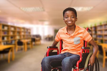 discapacitados: Retrato de niño sentado en la silla de ruedas en la biblioteca contra la vista de biblioteca